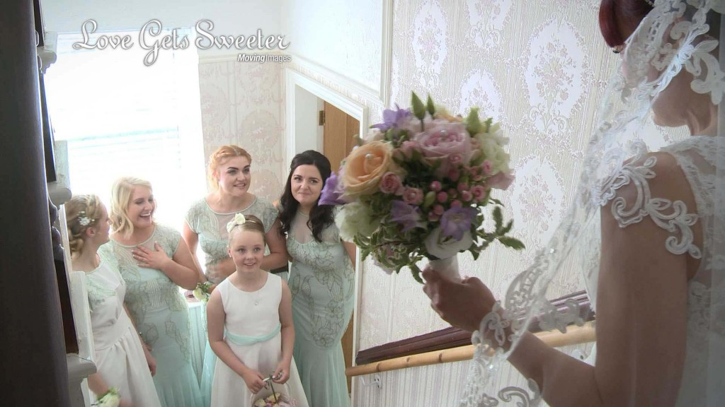 A group of bridesmaids gasp as their see their friend as a bride for the first time. She stands at the top of the stairs at her parents house in the wirral holding her bouquet for the wedding videographer