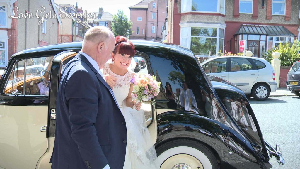 A still from Siobhan and Gary's wedding video of the bride stepping out on her cream and black traditional wedding car in to the sunshine with a huge smile on her face holding a bright pastel bridal bouquet in the Wirral