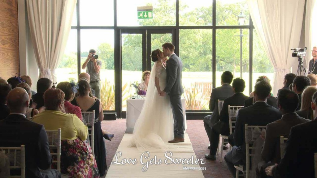 a still from their wedding video of a bride and groom kiss as their wedding guests clap and cheer after being announced husband and wife during their wedding ceremony at Rookery Hall in Nantwich