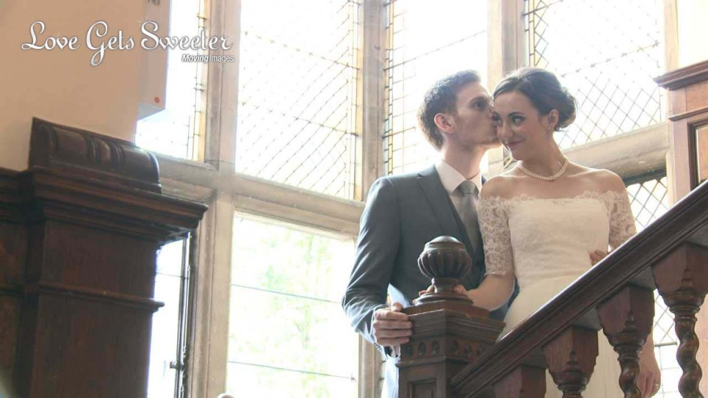 A groom kisses the cheek of his bride as they stand on the dark wooden staircase at Rookery hall to pose for the photo and video. She wears an off the shoulder lace vintage inspired wedding dress and pearl neckalace