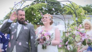 A wedding video still of groom bats away confetti as the bride laughs during their wedding reception at Rowton Hall