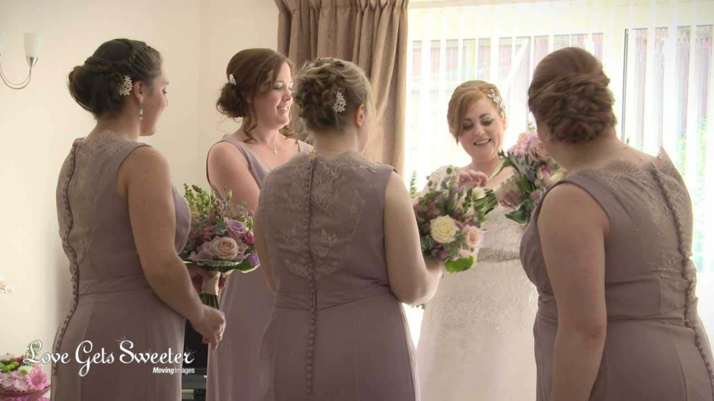 A video still of the bride surrounded by her 4 bridesmaids wearing a dusty pink dress with lace detailing. She passing out the flower bouquets of cream, pinks and dusty purples before they head to the church for her wedding