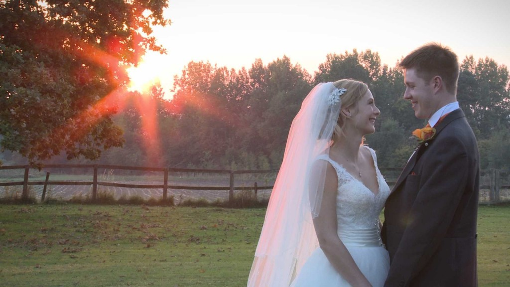 A bride and groom chat naturally as the sun sets during a winter wedding at Willington Hall