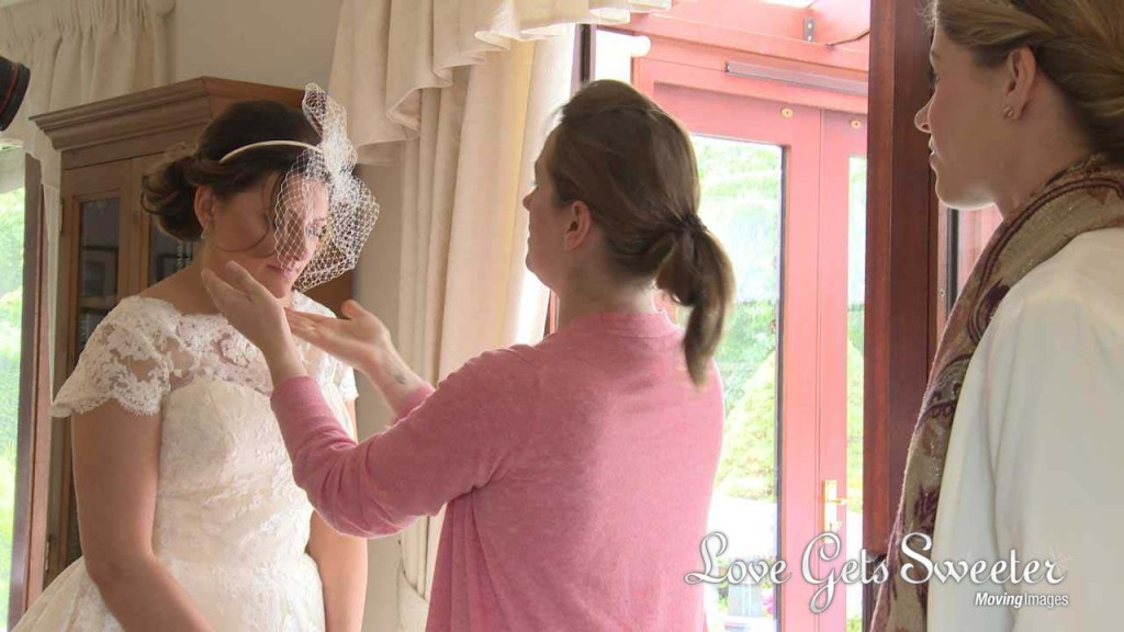 A wedding video still of Michelle Sisson helping a bride getting ready and having her vintage inspired birdcage veil adjusted before her wedding at Soughton Hall
