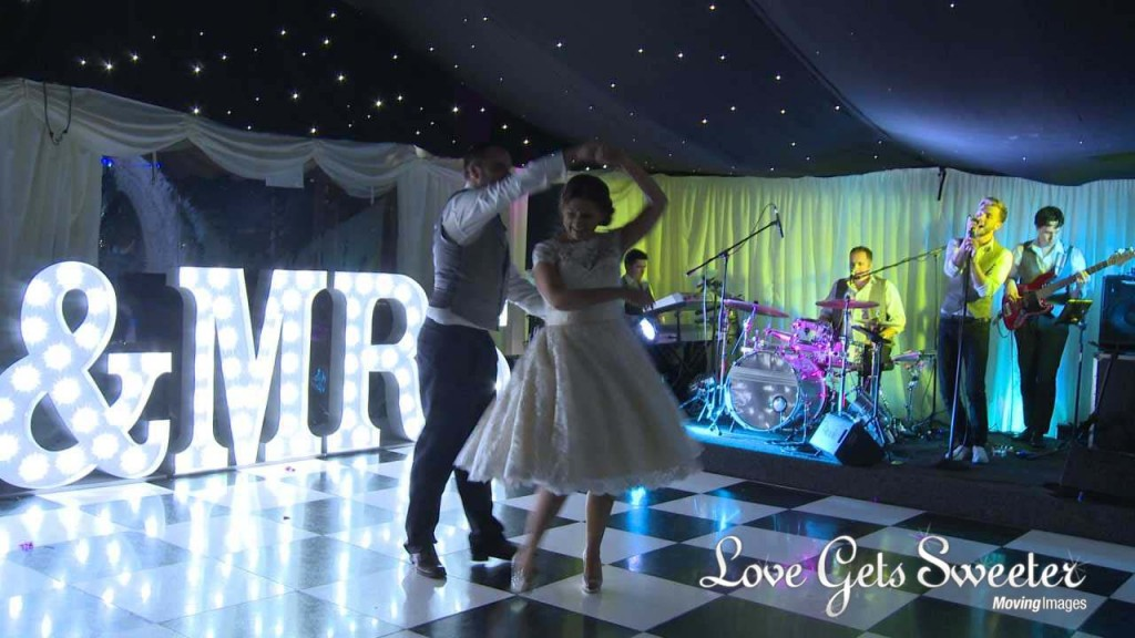 first dance at Soughton Hall in front of Mr and Mrs light up letters and the groom twirls his bride to make it a bit more fun as the band perform Take That for them