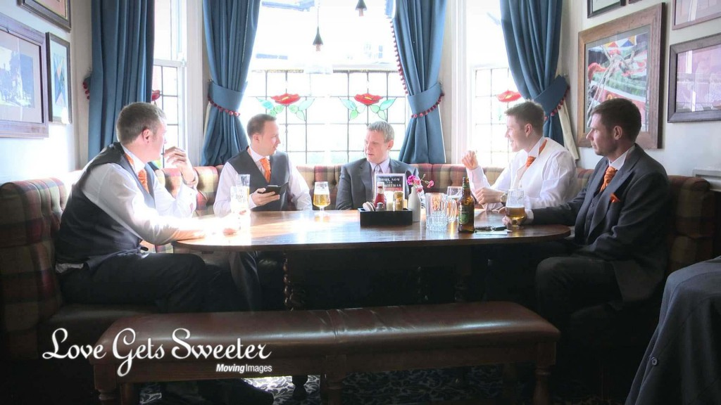 groom and groomsmen sit in a window booth at their local pub enjoying a pint before they head over to the wedding church in High Legh. They wear traditional morning suits with bright orange ties