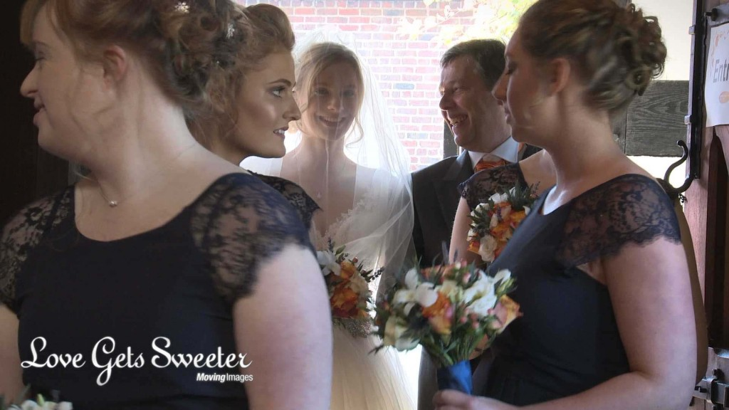 the wedding videographer films through the awaiting bridesmaids wearing navy and holding cream and orange bouquets to see the bride standing with her proud and smiling dad in the doorway to St Johns Church in High Legh