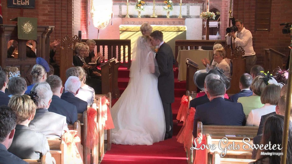the bride and groom enjoy their first kiss as husband and wife for the wedding video at St Johns in High Legh