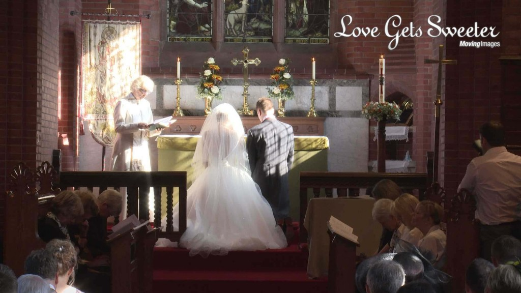 a bride and groom kneel at the alter during their wedding blessing at St John's Church in High Legh Cheshire and the wedding videographer films from the back as the sun shines down on them beautifully