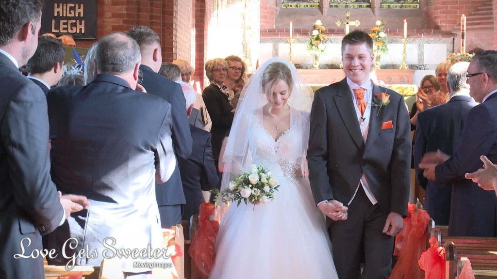 the shy bride looks down as the groom smile is wide. They walk down the aisle at St Johns in High Legh towards their wedding videographer Love Gets Sweeter
