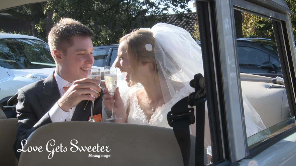 the bride and groom grin at each other as they clink champagne glasses and say cheers inside their Horgan wedding car