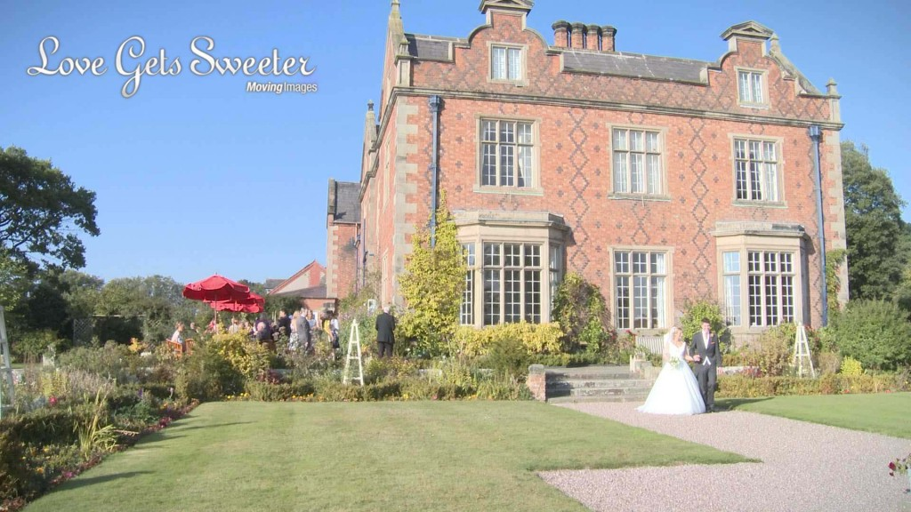 A wide shot of the side of Willington Hall in Cheshire. With bright blue skies and sunshine their wedding guests enjoy drinks on the patio as the wedding photographer and videographer film the bride and groom having a walk around the gardens
