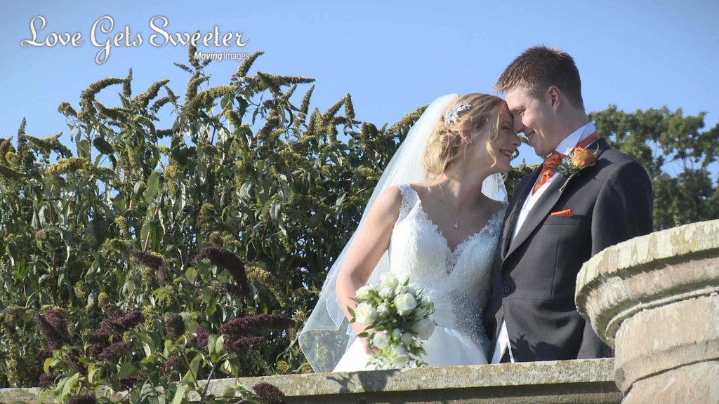 the bride leans in to the groom as they enjoy a laugh and giggle on the terrace at their wedding venue Willington Hall in Cheshire