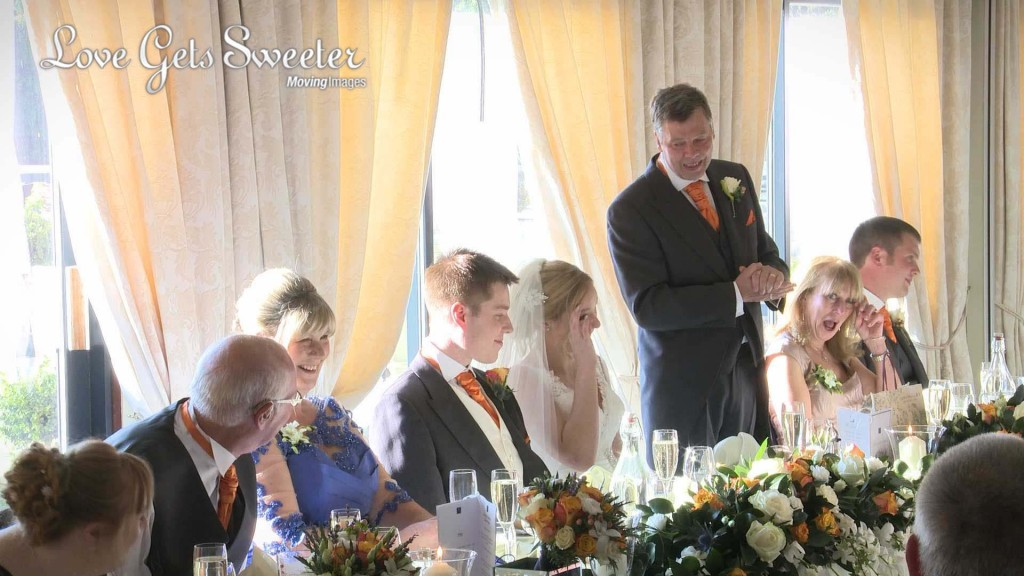 the father of the bride stands to give his wedding speech at willington hall and have the bride in tears as she gets emotional on the wedding video