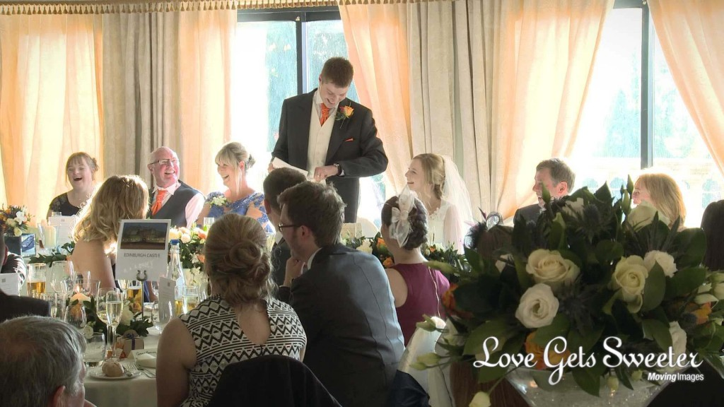 a shot from the wedding video of everyone laughing during the grooms wedding speech at Willington hall