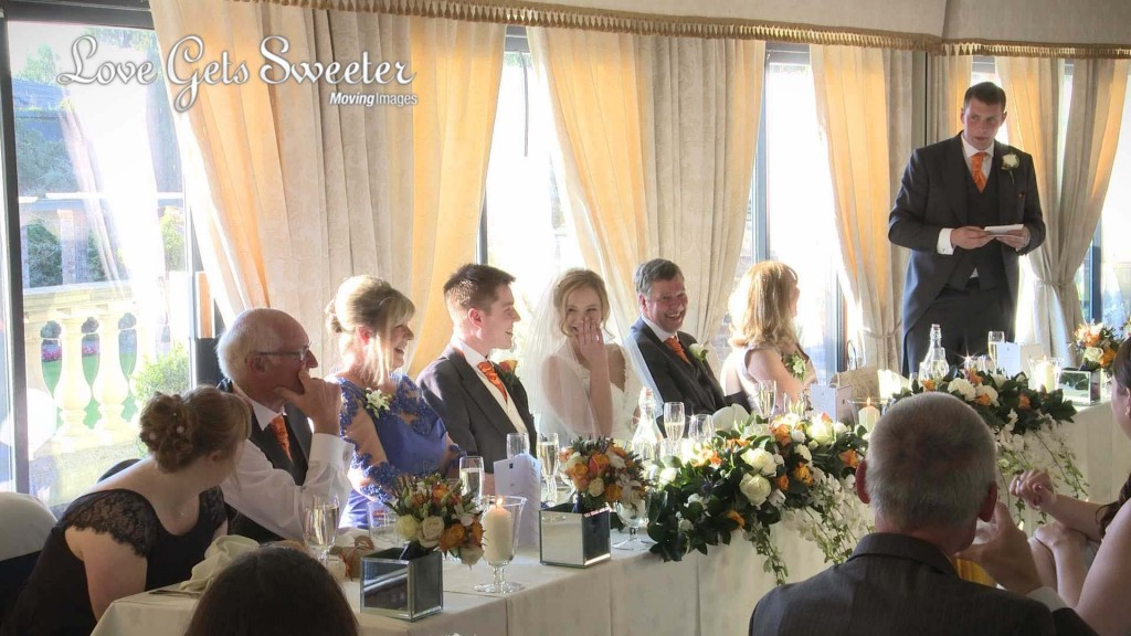 the bride covers her face with her hand as the best man tries to embarrass the groom during his best mans speech at Willington Hall