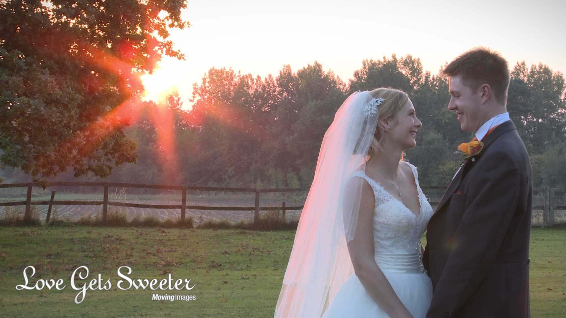 beautiful red sunset filmed by videographer with bride and groom posing for couple portraits in the garden at Willington Hall in Cheshire