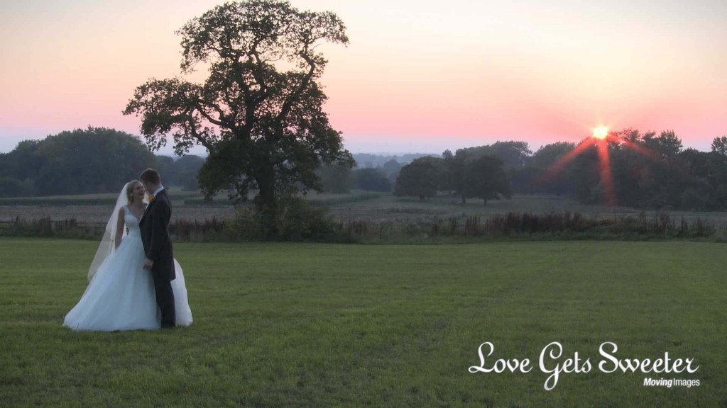 A still from the wedding video of the wedding videographer filming the bride and groom enjoying some time together at dusk in front of a beautiful sunset outside Willington Hall in Tarpoley Cheshire