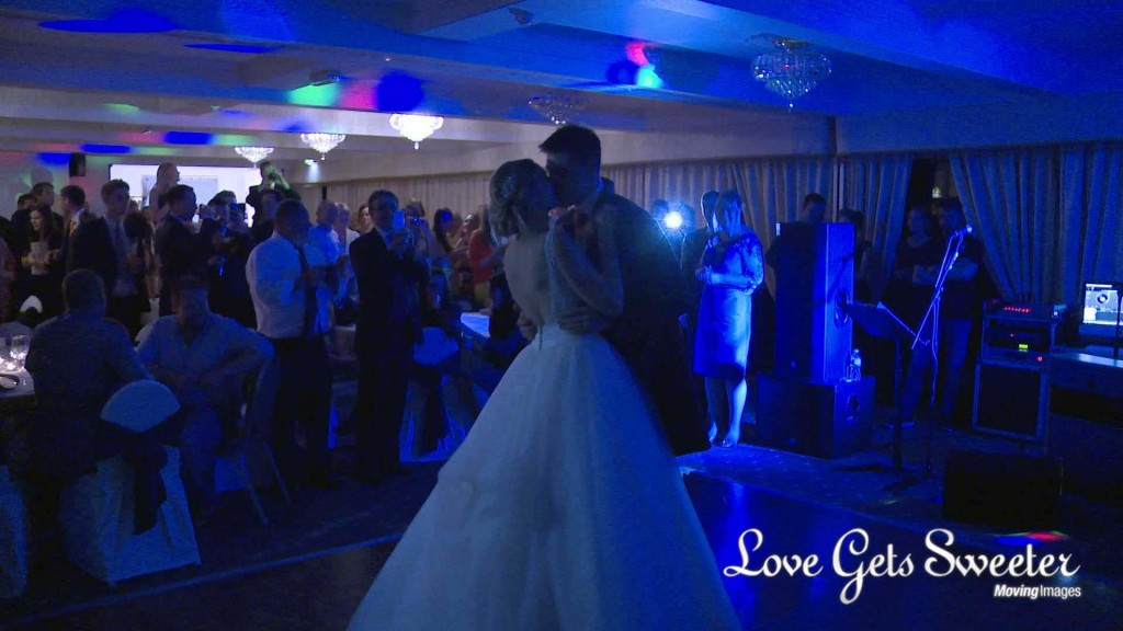 a still from the wedding video of the bride and grooms first dance at their Willington Hall wedding. They enjoy a kiss as everyone cheers
