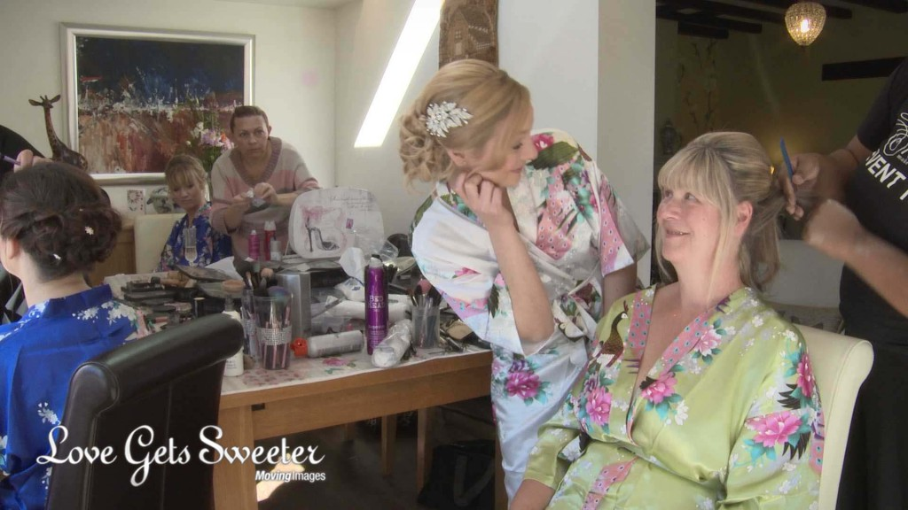 Emma the bride leans in front of her mum and they smile at each other as she enjoys having her hair done for her daughters wedding at Willlington Hall
