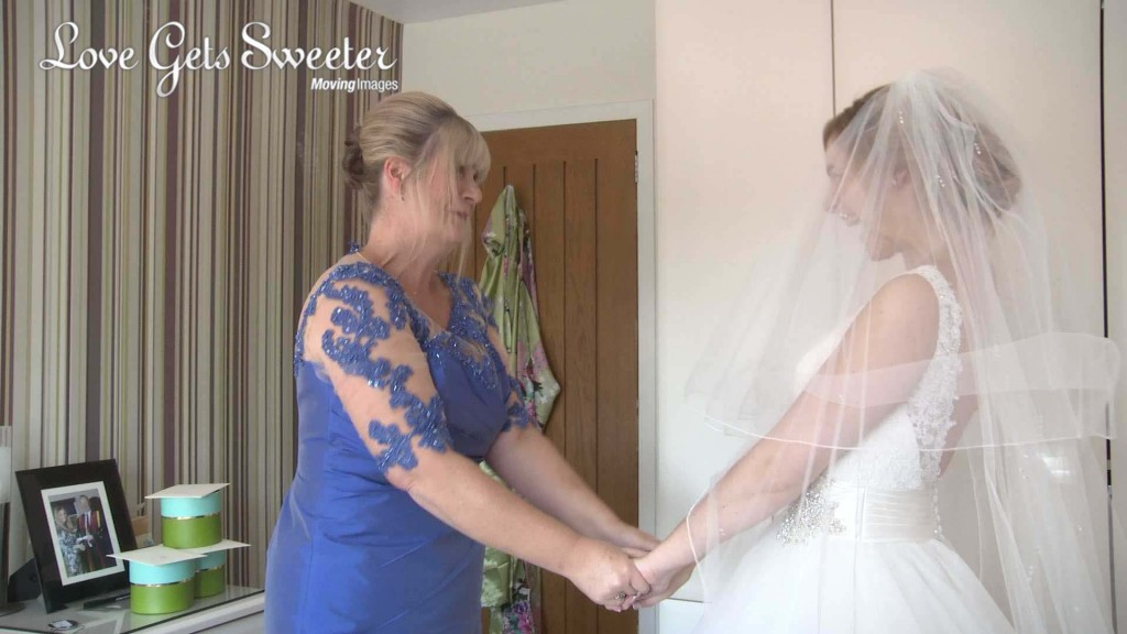 the bride and her mum hold hands once she's in her wedding dress. The wedding videographer captures a natural moment as the mum looks on proudly and the bride gives an excited wide grin before she goes to show her Dad and bridesmaids for their first look