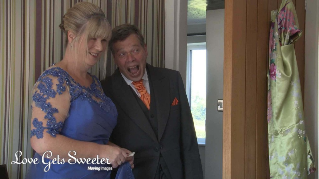 A dad walks in and gasps as he sees his daughter the bride for the first time in her wedding dress in Cheshire. Captured on the wedding video by wedding videographer Love Gets Sweeter