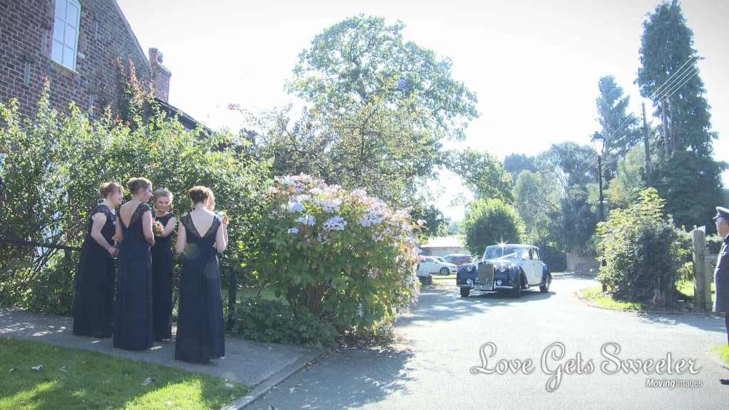 the bridesmaids in their floor length navy bridesmaid dresses wait on the path to the church as the navy and blue 'emma' Horgans wedding car comes round the corner with the bride and her Dad as the wedding videographer waits