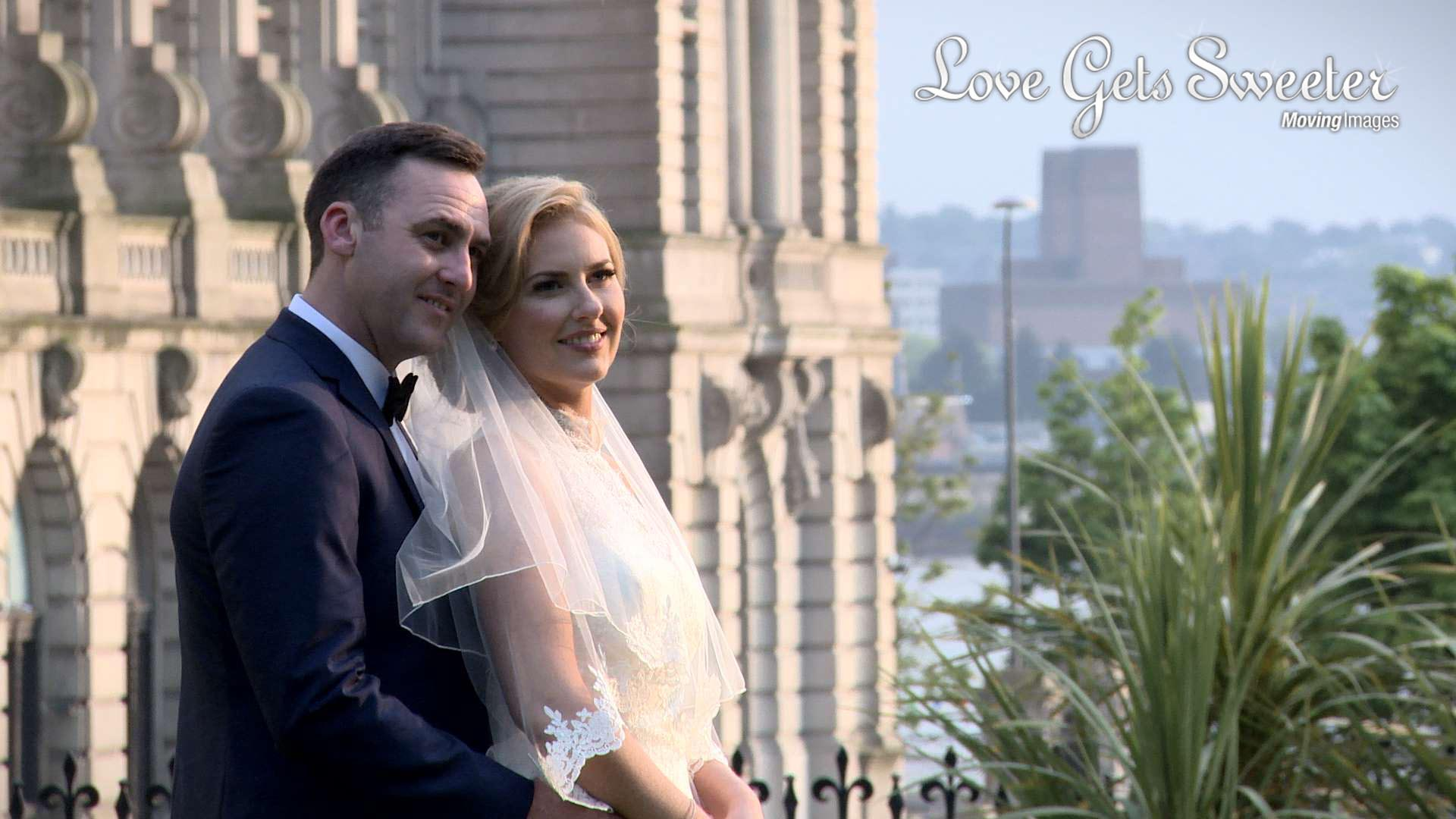 Bride and Groom posing for photographs in St Anne's Church gardens near the Liver Buildings after their wedding ceremony