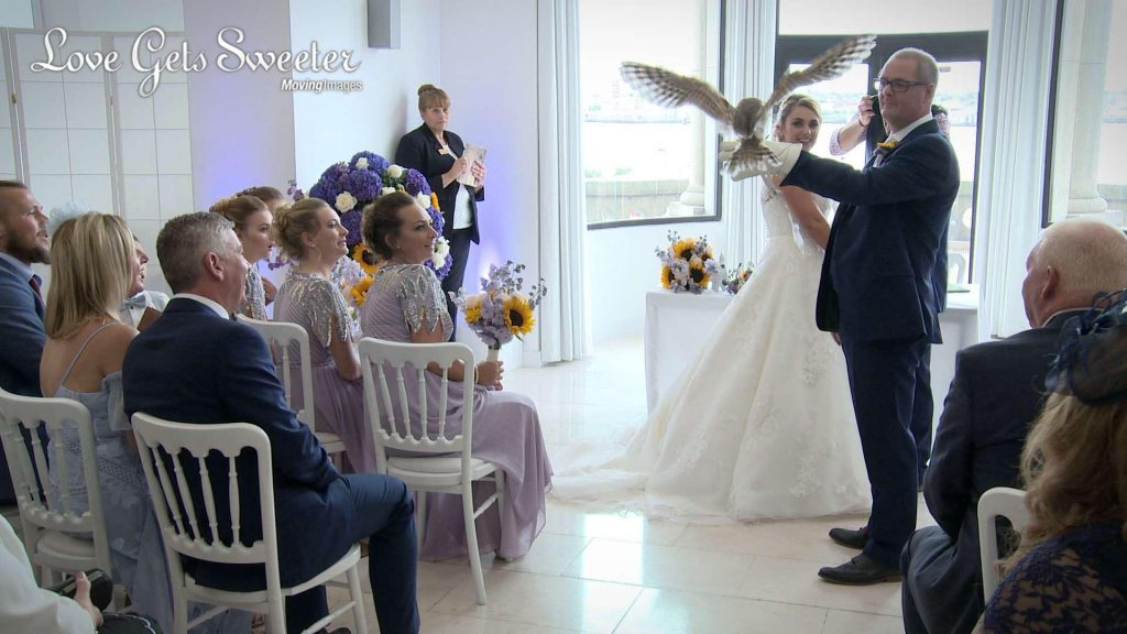 An owl swoops in to land on the best man's arm to deliver the wedding rings to the waiting bride and groom during their wedding ceremony at The Venue at The Royal Liver Building by the Albert Dock