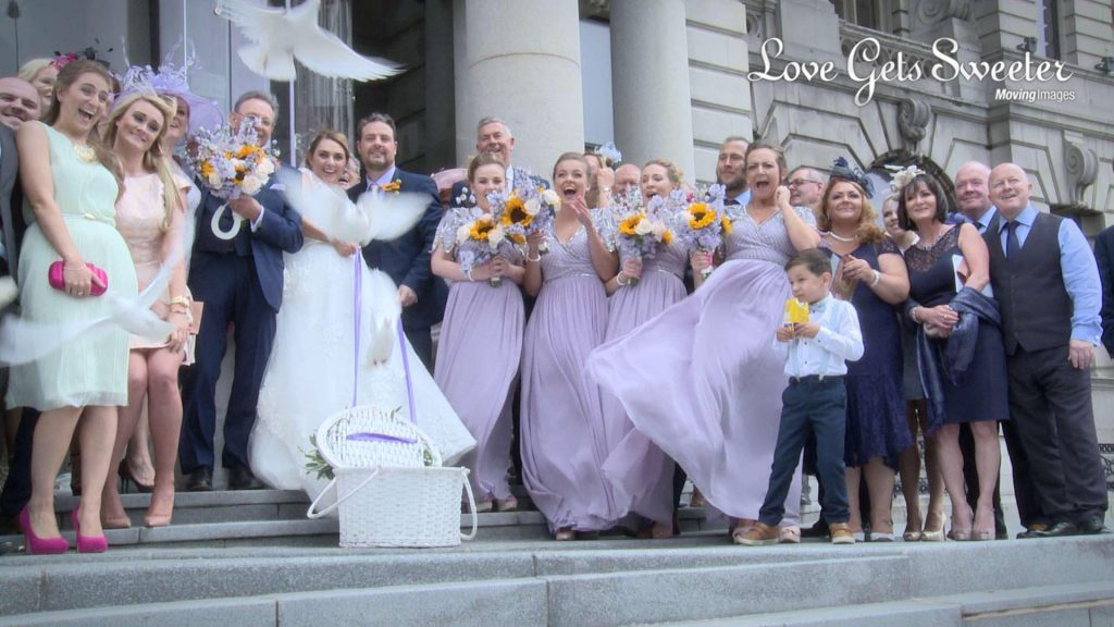 wedding guests squeal and cheer as two white doves are released from a white basket by the bride and groom after their wedding at the Royal Liver building on the Liverpool waterfront