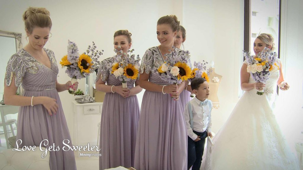 A shot from the wedding video of the Bride and her bridesmaids waiting before the wedding ceremony at The Venue in the Royal Liver Building in Liverpool. They were long floor length pale purple bridesmaid dresses with beaded detail on the shoulders and hold oversized bouquets of pale pink roses, purple flowers and yellow sunflowers