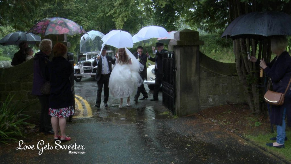 the driver from broughton wedding cars helps the father of the bride and the bride get to the church dry with white umbrellas to stop the rain