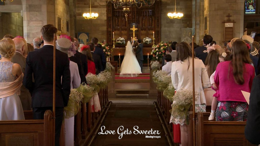 the bride and groom light a candle during the wedding ceremony at st johns church in broughton Preston