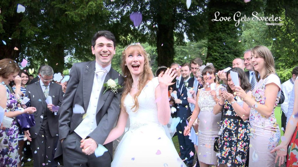 the bride and groom pose covered in purple heart shaped colourful wedding confetti outside mitton hall lancashire