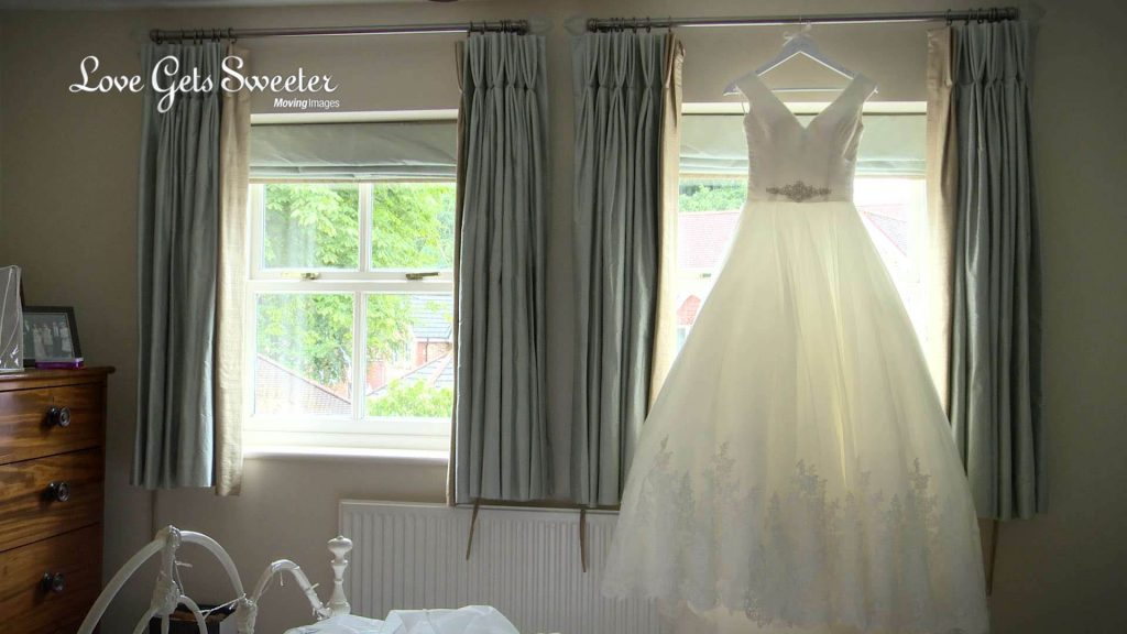 The brides traditional wedding dress with lace applique detailing hangs in the window of her parents house near Preston in Lancashire
