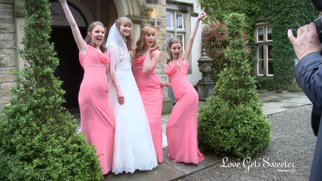 the bridesmaids dressed in full length pink dresses pull funny poses or the wedding photographer outside mitton hall