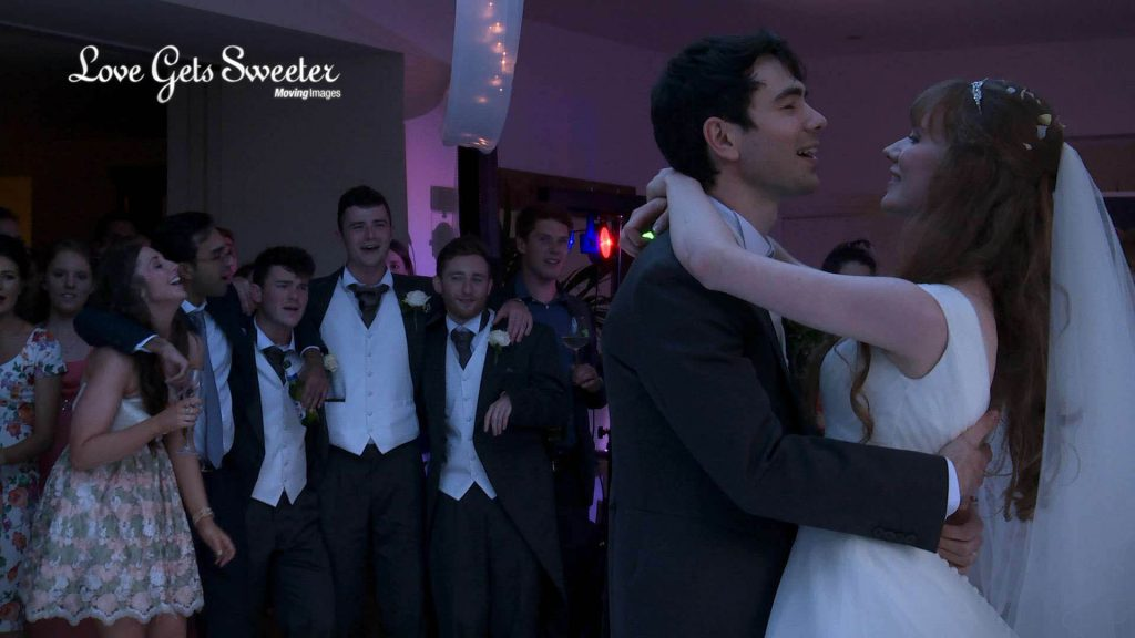 wedding guests sing along with the wedding band during the first dance on this mitton hall wedding video