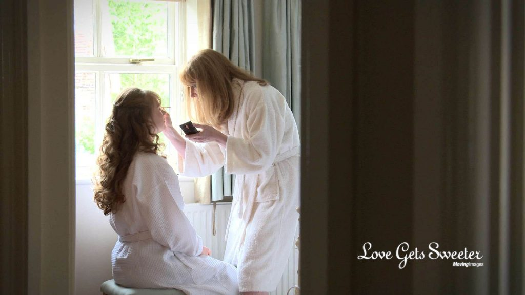 The wedding videographer is peering through the bedroom door filming the mother of the bride doing her daughters make-up in the beautiful natural light of the window