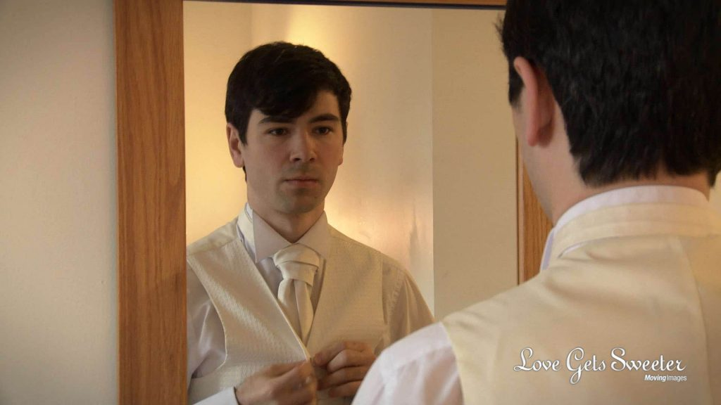 The groom stands in front of a mirror to check his cream wedding tie and waistcoat
