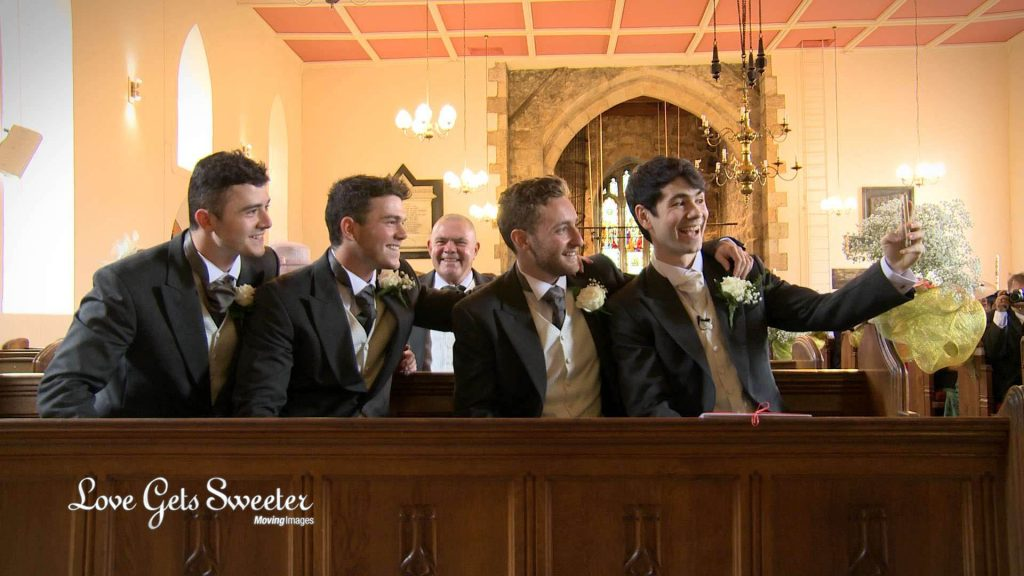 The groom, best man and ushers pose for a selfie sat in the front pew of st johns church in broughton near preston on their wedding video
