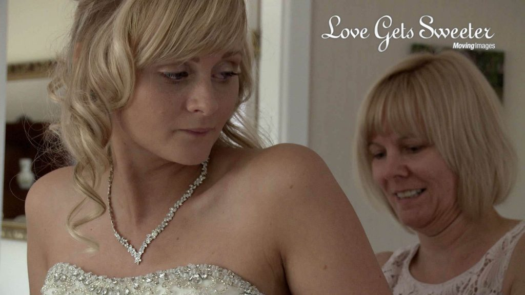 bride being helped in to wedding dress in Sandbach