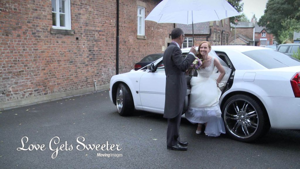 dad helps daughter get out of the bentley wedding car holding an umbrella in the rain