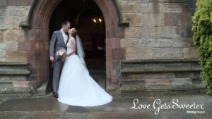 bride and groom kiss under the archway outside church showing off brides bespoke dress