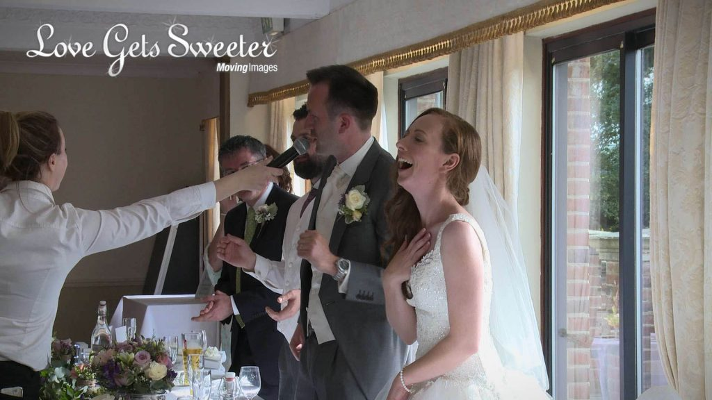 Groom singing in to the mic during Singing Waiters performance after meal at Willington Hall