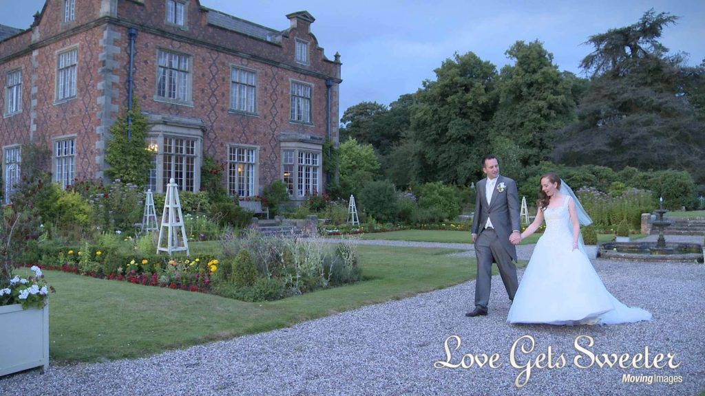 bride and groom taking a romantic walk around the stunning gardens at sunset at willington hall in Cheshire