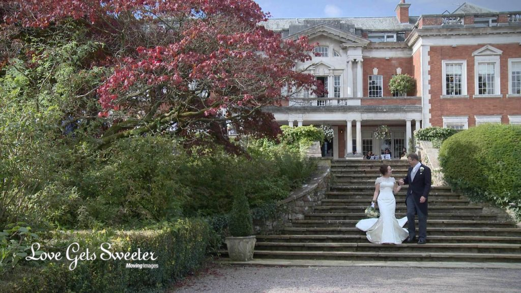 bride and groom walking around the summer gardens in front of Eaves Hall in Cheshire for the female wedding videographer