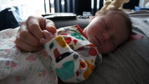 Daddy holding sleepy babys hand while filming for a newborn lifestyle shoot in burscough, lancashire