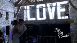 bride and grooms first dance at Plas Isaf country barn in front of giant LOVE letters
