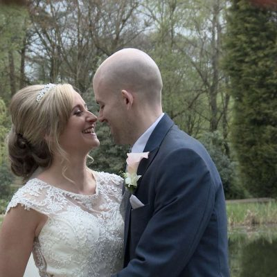 bride and groom having a cuddle and kiss beside the lake at Moddershall Oaks wedding venue for their wedding video