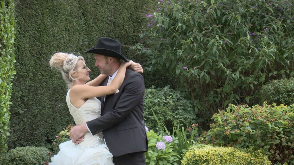 bride wearing Ian Stuart wedding dress and cowboy groom in a black stetson during their farm wedding in Yorkshire